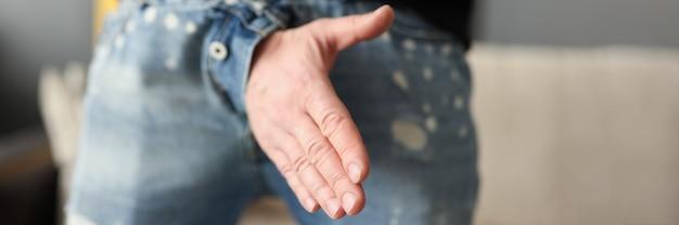 L'uomo offre una stretta di mano attraverso la patta dei pantaloni