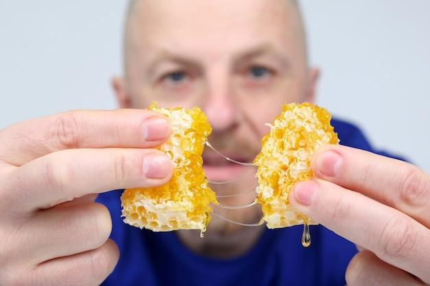 L'uomo offre un pezzo di miele a nido d'ape