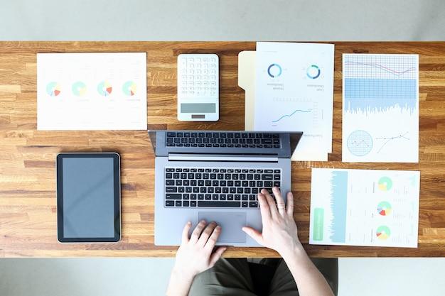 L'uomo in ufficio inserisce i dati dal rapporto nel computer portatile