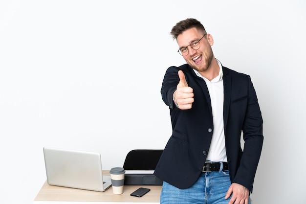 Uomo in un ufficio isolato sul muro bianco con il pollice in alto perché è successo qualcosa di buono