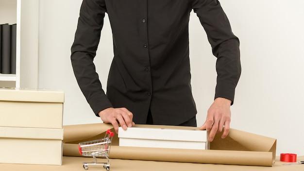 L'uomo in un ufficio confeziona un regalo di pacchi postali per la spedizione