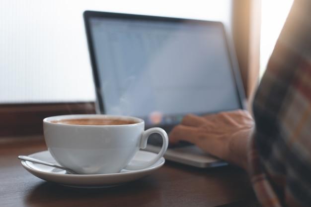 Uomo online che lavora al computer portatile al bar
