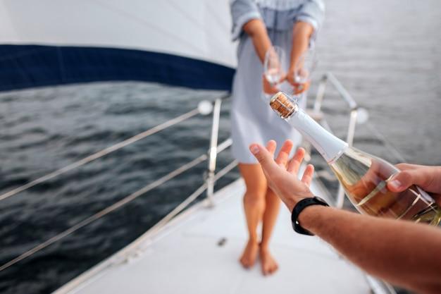 L'uomo apre una bottiglia di champagne nello yacht di lusso. Foto Premium