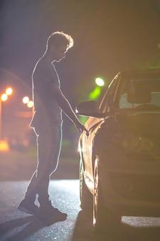 L'uomo apre l'auto sulla strada. sera notte