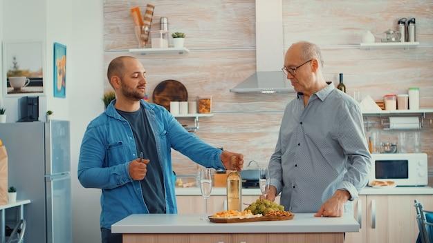 Uomo che apre una bottiglia di vino in una cucina moderna circondata dalla famiglia. padre e figlio stanno insieme intorno al tavolo, discutendo e servendo un bicchiere di vino bianco.
