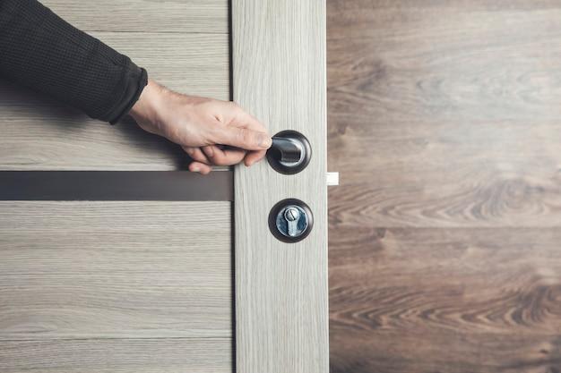 Uomo che apre la porta di legno della camera.