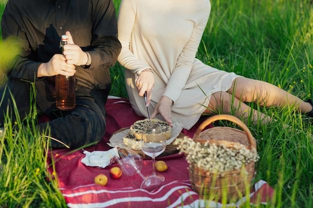 L'uomo apre la bottiglia di vino mentre la donna taglia una gustosa cheesecake