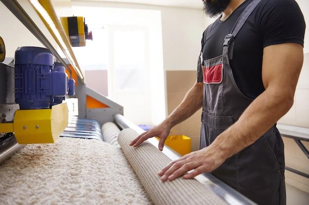 Uomo che opera la lavatrice automatica del tappeto nel servizio di lavanderia professionale