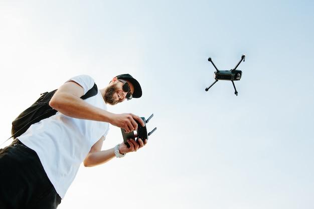 Uomo che aziona il drone tramite telecomando e si diverte