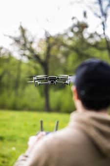 Uomo che opera drone volante o in bilico tramite telecomando in natura