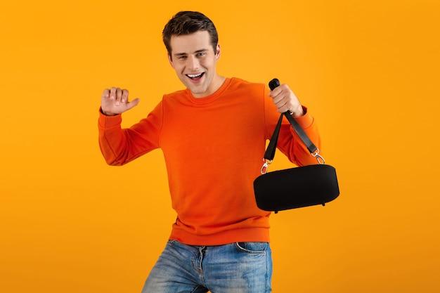 Uomo in maglione arancione con altoparlante wireless felice ascolto di musica divertendosi isolato su giallo