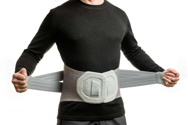Uomo in un corsetto ortopedico isolato sul muro bianco