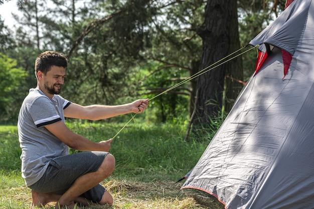 Un uomo all'aperto in procinto di montare una tenda.