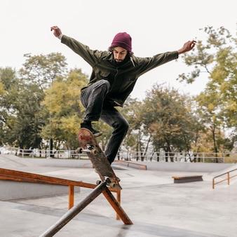 Uomo all'aperto con lo skateboard nel parco