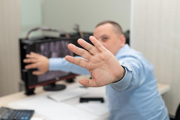 L'uomo ha la mano tesa e mostra il segnale di stop con la mano che rifiuta o vieta le foto controllo di sorveglianza