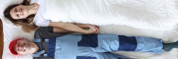 Uomo in generale idraulico sdraiato a letto con donna vista dall'alto concetto di infedeltà femminile