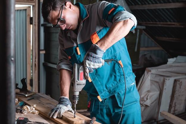 Uomo in tuta e occhiali nell'officina in un trapano, trapano una tavola di legno
