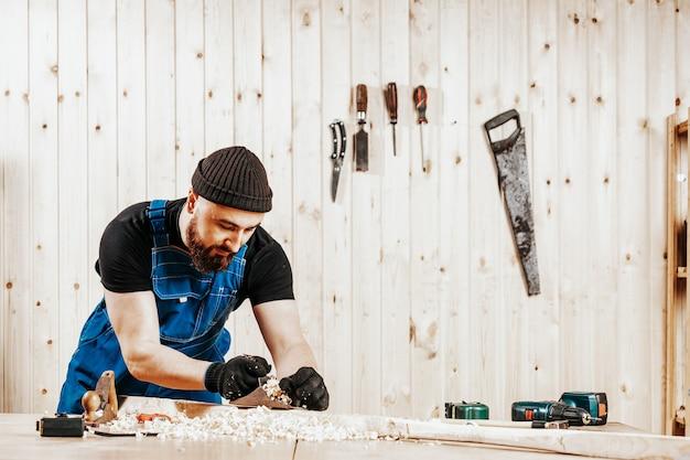 Uomo in tuta che tratta una barra di legno con un aereo da blackjack