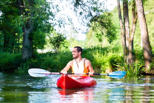 Uomo che rema con la canoa o il kayak sul fiume