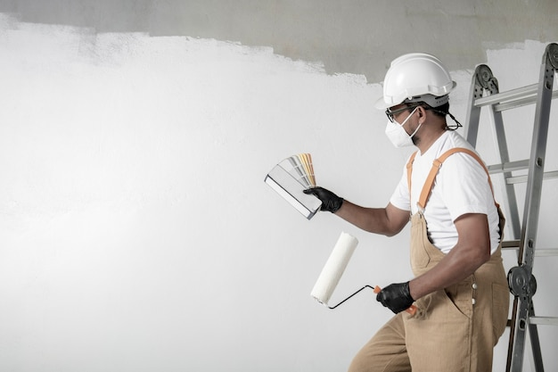 Un uomo dipinge un muro bianco con un rullo