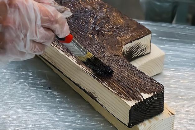 L'uomo dipinge una scatola di legno. il costo copre la tavola in legno lakme con intagli a mano. fatto a mano su legno. utensili da cucina laccati. antico mestiere slavo ucraino russo.