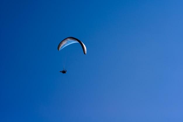 Uomo su un paracadute che vola in chiaro cielo