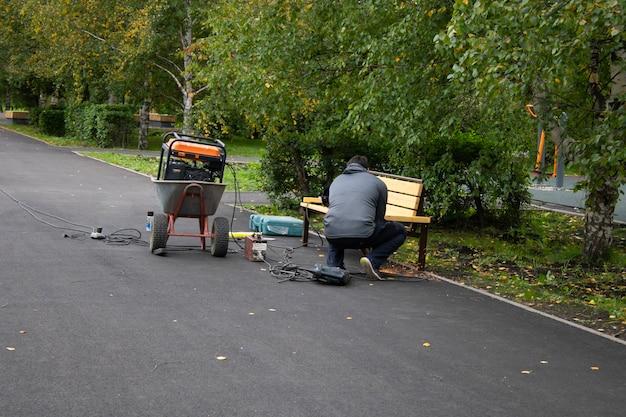 Un uomo nel parco conduce lavori di saldatura un lavoratore installa un banco saldando apparecchiature per la saldatura