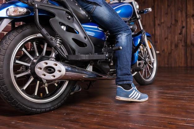 Uomo che parcheggia la sua moto al chiuso su un pavimento di legno con il piede a terra, vista ad angolo basso del pneumatico posteriore e del piede