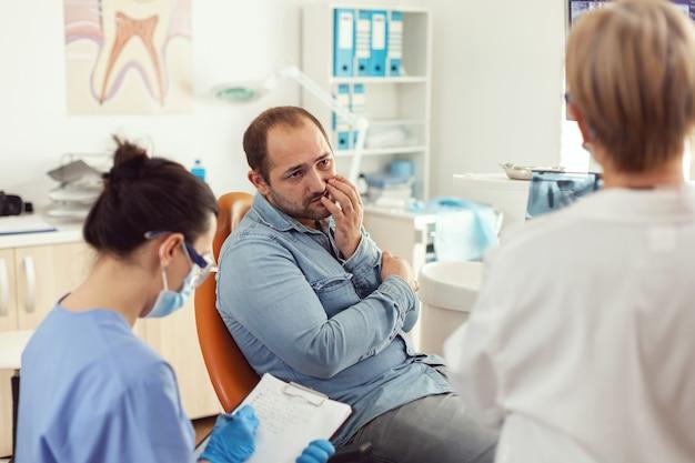 Paziente uomo con dolore ai denti che spiega il problema dentale all'infermiera