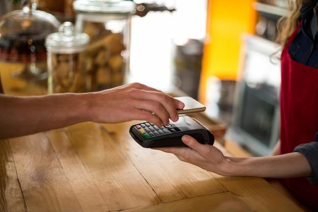 Uomo che paga la fattura tramite smartphone utilizzando la tecnologia nfc