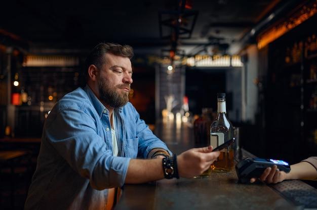 L'uomo paga per telefono al bancone del bar, pagamento senza contatto. la persona di sesso maschile mette lo smartphone al terminale in pub, moderne tecnologie sicure