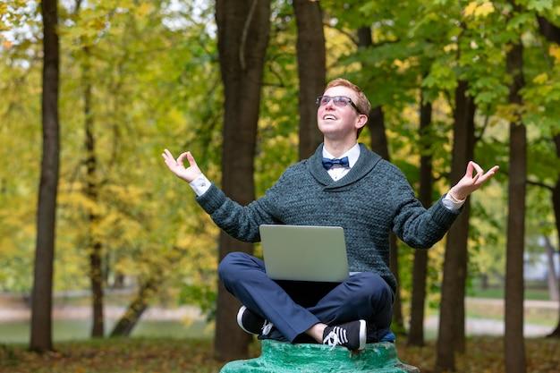 Un uomo su un piedistallo che finge di essere una statua medita nella posizione del loto nel parco.