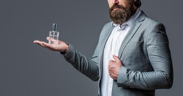 Profumo uomo, fragranza. profumeria maschile, uomo barbuto in abito. maschio tenendo in mano una bottiglia di profumo.