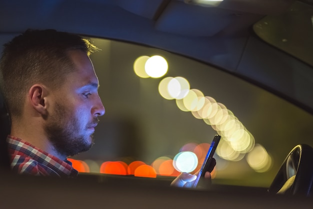 Il telefono dell'uomo all'interno dell'auto in autostrada. sera notte