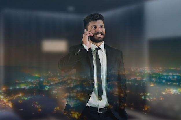Il telefono dell'uomo vicino alla finestra con le luci della città