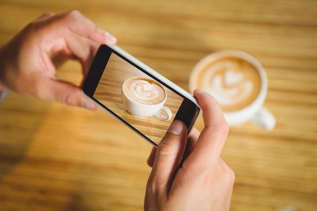Uomo che fotografa il suo cappuccino con caffè art