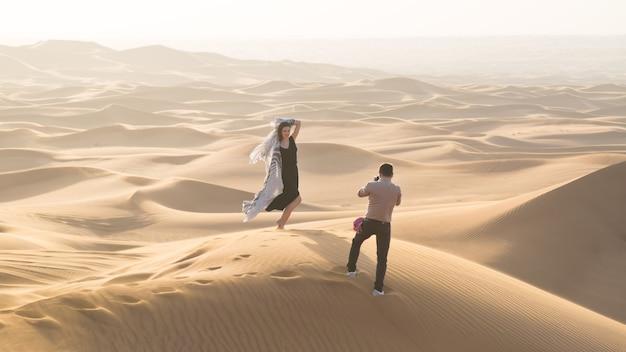 Un uomo fotografa una giovane donna nelle sabbie del deserto durante un servizio pubblicitario per una rivista