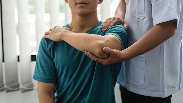 Fisioterapista dell'uomo che assiste paziente maschio con infortunio al gomito in clinica.