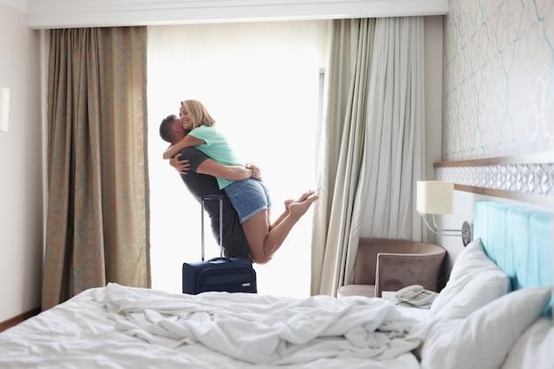 Uomo che prende la donna nella camera d'albergo con la valigia