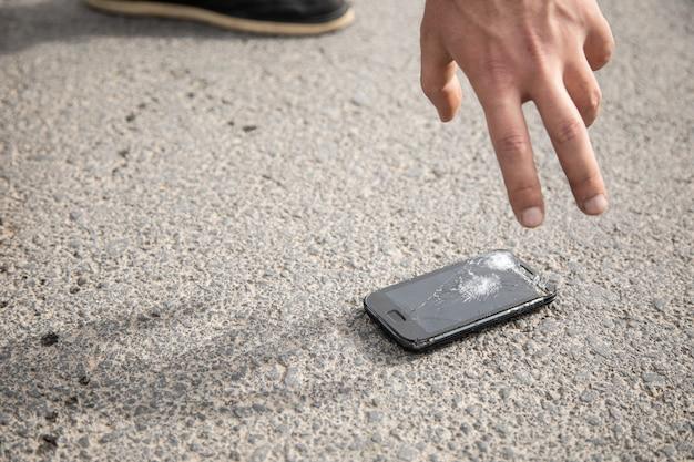 Un uomo prende in mano un telefono rotto