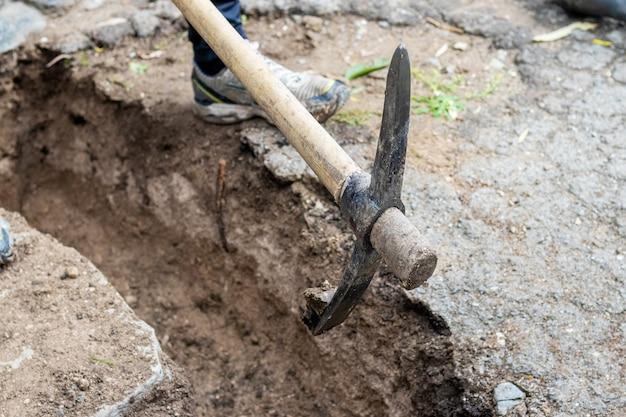 Un uomo raccoglie un terreno duro con un piccone mentre scava un fossato in un cantiere edile