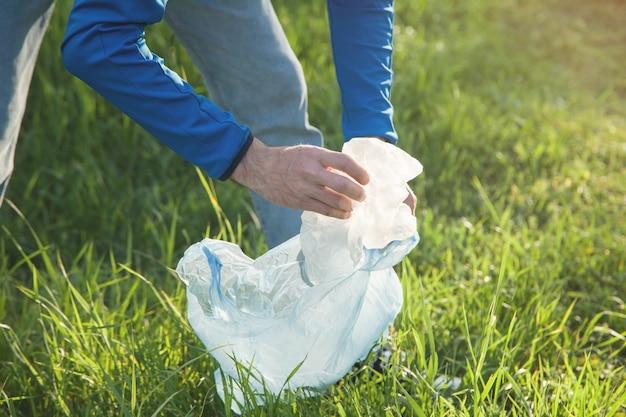 L'uomo prende un sacchetto di plastica da un parco erboso.