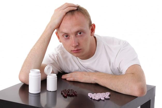 Uomo e pillole isolati su bianco