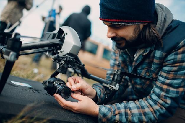 Pilota dell'uomo che controlla la fotocamera del drone quadricottero prima del volo aereo e delle riprese