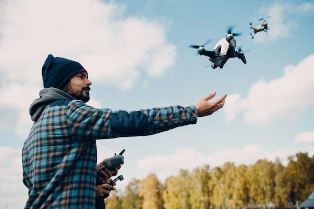 Pilota uomo che controlla drone quadricottero con telecomando pad