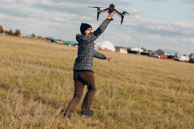 Pilota dell'uomo che tiene in mano un drone quadricottero e corre in un campo all'aperto