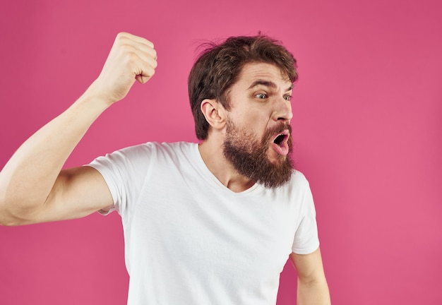 Uomo su sfondo rosa stress irritabilità aggressività gesticolando con le mani vista ritagliata. foto di alta qualità