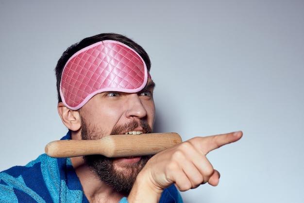 Un uomo in una mascherina rosa del sonno tiene un mattarello nelle sue mani e veste blu del modello di aggressione energetica di emozioni