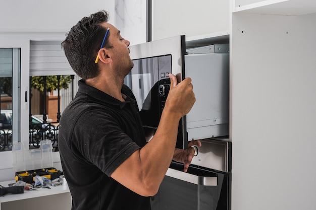 Uomo che mette un forno a microonde nel buco di un nuovo mobile da cucina