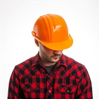 Un uomo con una camicia a quadri e un casco da costruzione isolato